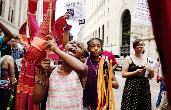 """Haley Nelson/Post-Gazette Ten-year-old Aniyah Grayson of the Hill District leads her friends Friday in the """"Still We Rise"""" march, Downtown. Aniyah represented the Jeron X. Grayson Community Center, and she is the niece of the man who the community center was named for."""