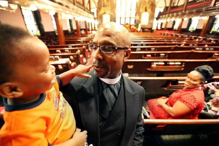 The Rev. Eric S.C. Manning, new pastor of Emanuel AME Church, and 2-year-old Teddie Pryor III get to know one another before Vacation Bible School begins at the downtown church on Wednesday. WADE SPEES/STAFF