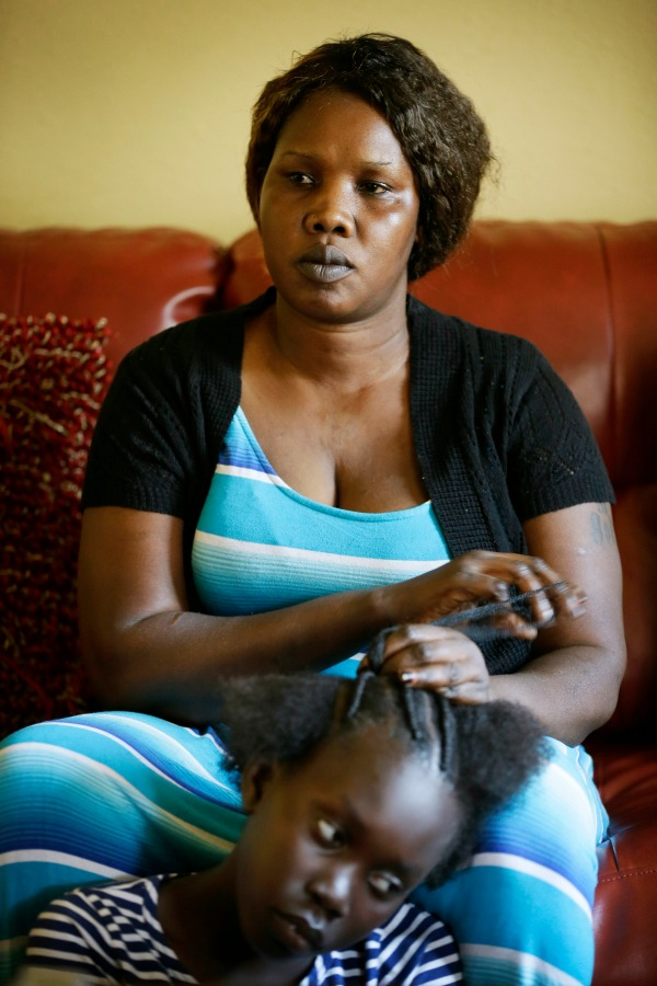 Achan Agit, of Des Moines, Iowa, braids nine-year old Esta James' hair, Wednesday, June 22, 2016, in Des Moines, Iowa. Agit is one of two women challenging Iowa's regulation on African-style hair braiding that plan to drop a lawsuit they filed last year because of a change in state law. (AP Photo/Charlie Neibergall)